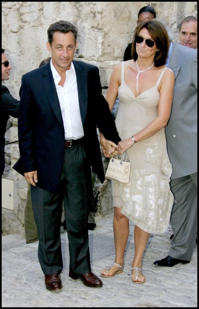 En juillet 2006, avec Cécilia Sarkozy : costume noir et chemise ouverte