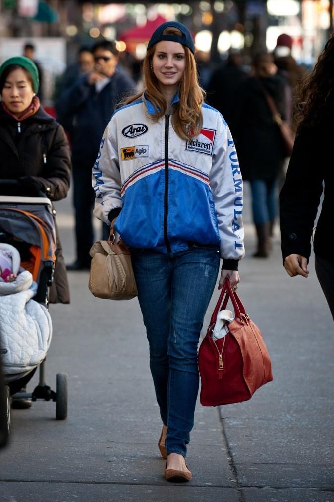 """Dans les rues de New York, Lana en jeans et blouson large pousse le style """"teenager"""" encore plus loin, en portant sa casquette à l'envers."""