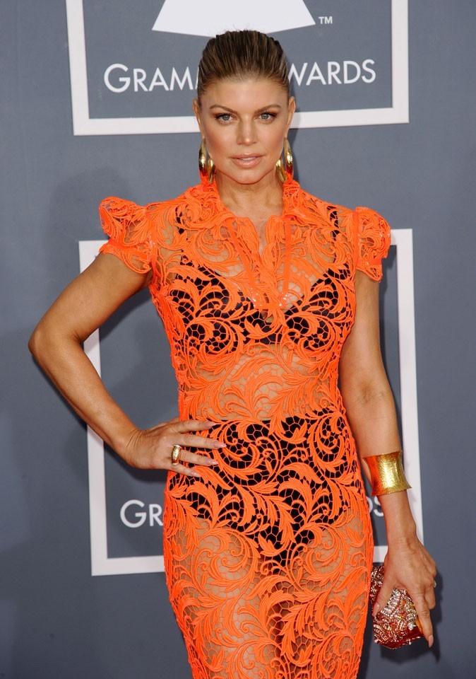 Fergie, fraîche et sexy en robe en dentelle orange Jean Paul Gaultier. On craque pour sa manchette dorée et ses grandes créoles assorties.