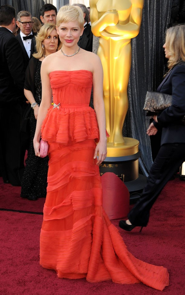 Michelle Williams en 2012 dans une robe bustier à volants de couleur rouge corail signée Louis Vuitton