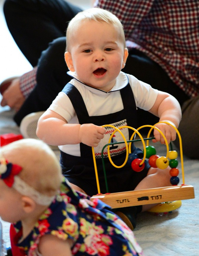 9 avril 2014 : Tandis que maman fait son devoir, ici pour l'association Plunket, George, lui, n'en revient pas de tous ces jouets !