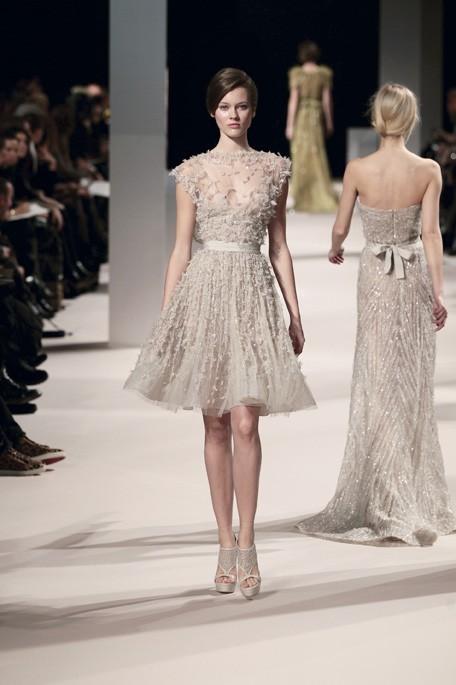 Robe courte effet corolle en tulle blanc craie brodé de paillettes ton sur ton, buste transparent, de la collection Haute Couture Printemps Eté 2011 Elie Saab
