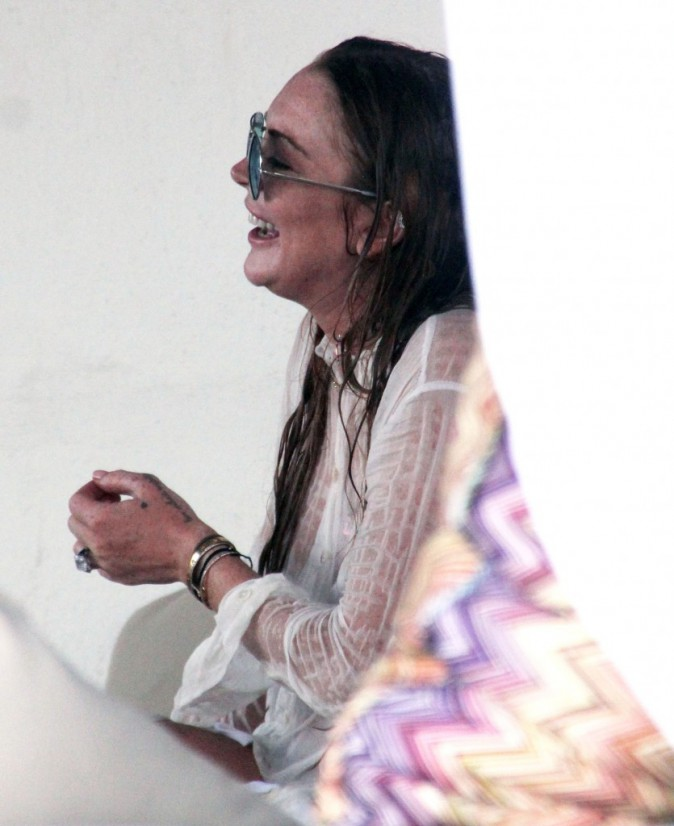 Lindsay Lohan passe du bon temps sur une plage à Mykonos en charmante compagnie le le 5 août 2014.